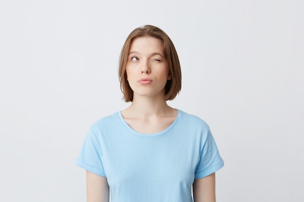 Thoughtful concentrated young woman in blue t shirt with one closed eyes thinking and trying to remember answers