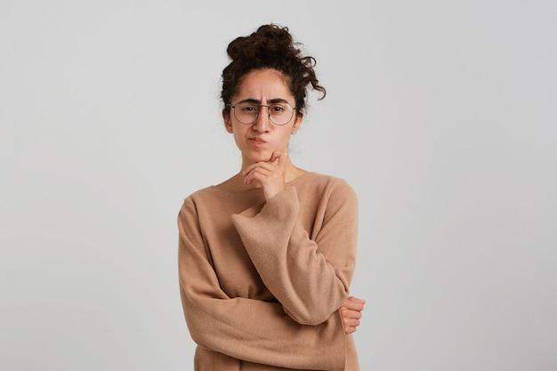 Giovane donna premurosa concentrata con chignon di capelli ricci scuri