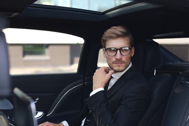 차에 앉아있는 동안 멀리보고 안경과 전체 정장에 사려 깊은 자신감 사업가.