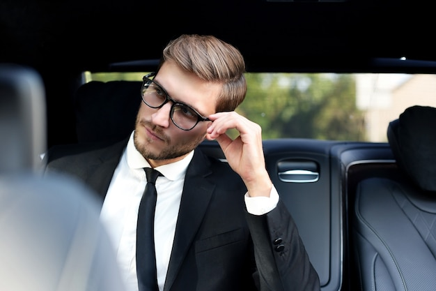 Thoughtful confident businessman keeping hand on glasses while sitting in the luxe car.