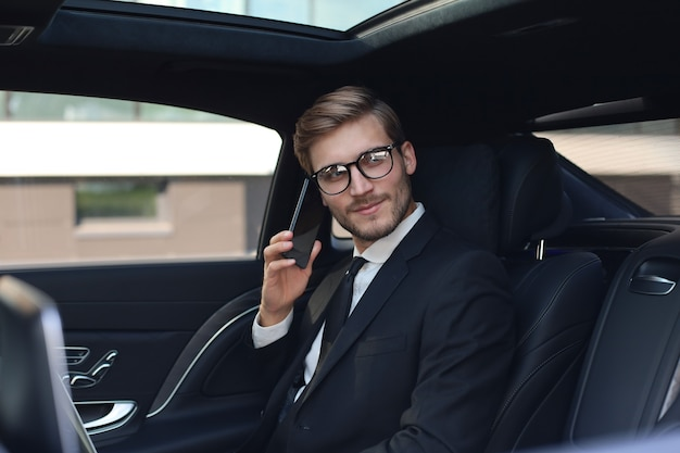 Thoughtful confident businessman talking on the phone while sitting in the car.