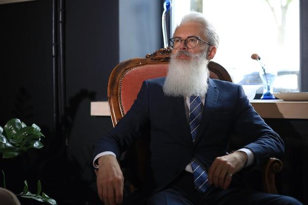그의 현대적인 사무실에서 안락의자에 앉아 비즈니스 개념에 대해 생각하는 사려 깊은 자신감 있는 잘생긴 사업가.