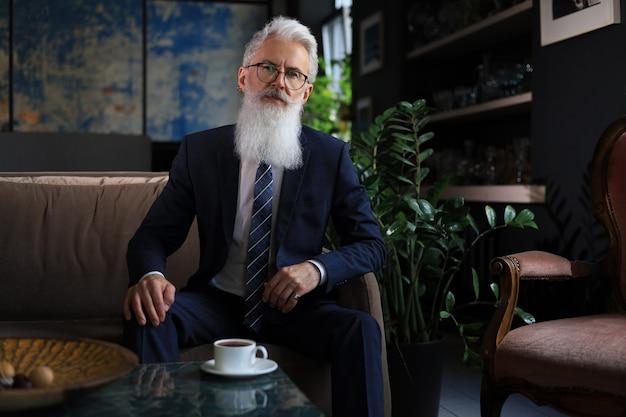 사려깊은 자신감 있는 잘생긴 사업가가 비즈니스 개념에 대해 현대적인 사무실에서 소파에 앉아 생각합니다. 휴식 시간.