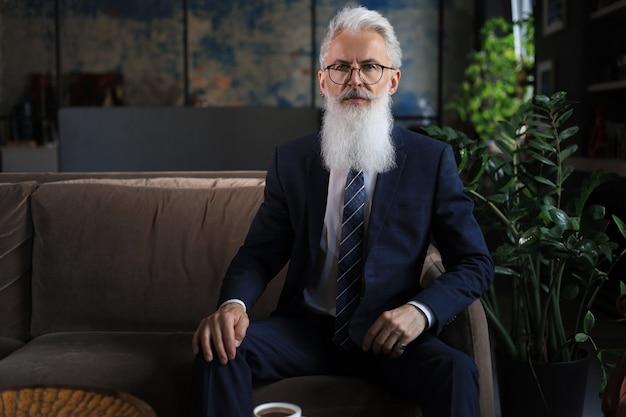 사려깊은 자신감 있는 잘생긴 사업가가 비즈니스 개념에 대해 현대적인 사무실에서 소파에 앉아 생각합니다.