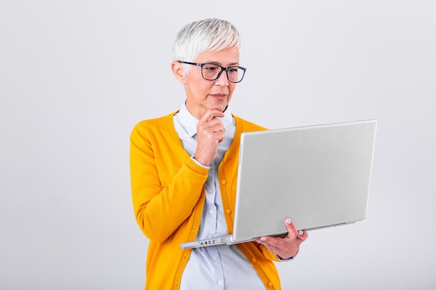 Thoughtful confused mature business woman concerned thinking about online problem looking at laptop, frustrated worried senior female  suffering from memory loss