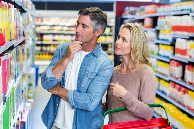 Thoughtful couple choosing a product at supermarket