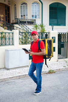 Thoughtful courier looking for house and holding tablet. professional deliveryman in red cap and shirt carrying yellow thermo bag with express order. delivery service and online shopping concept