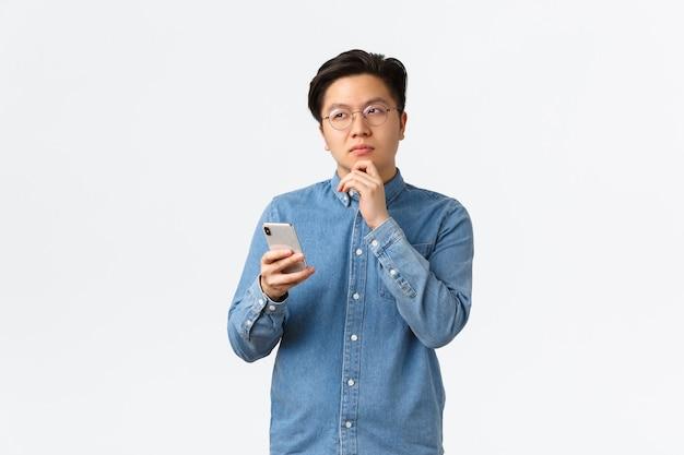 Uomo asiatico creativo premuroso con gli occhiali che pensa mentre pubblica post sui social media, distoglie lo sguardo, medita o prende una decisione, tiene in mano uno smartphone, sceglie qualcosa su internet.