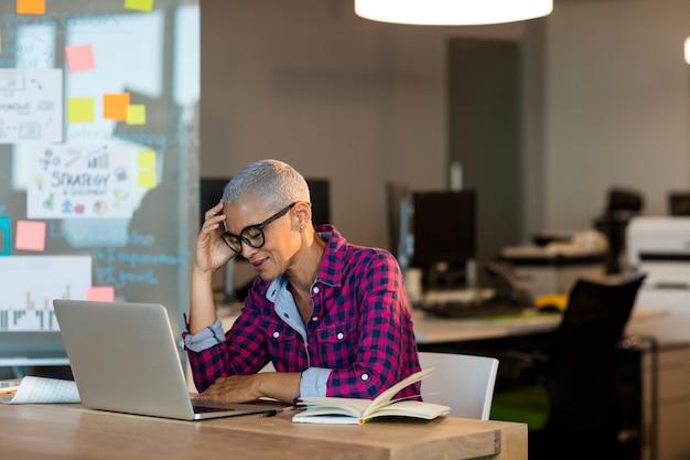 Вдумчивый творческий бизнесвумен, сидя на столе в офисе