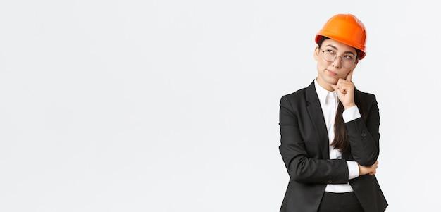 Riflessivo creativo capo architetto asiatico femminile, ingegnere edile che pensa, indossa casco e tuta di sicurezza, meditando la scelta migliore per la costruzione, in piedi sfondo bianco