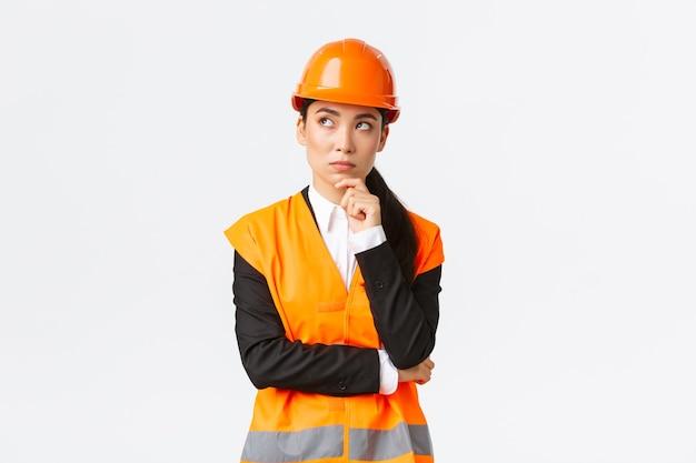 安全ヘルメット、反射ジャケット、左上隅を見て、考えて、解決策を探している思慮深い創造的な女性アジア人エンジニア。プロジェクトについて熟考している建設マネージャー