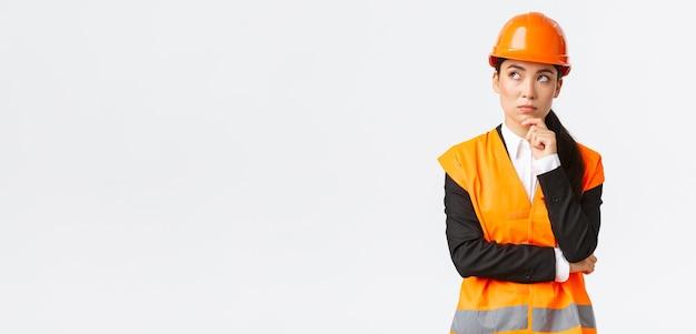 Вдумчивый творческий азиатский инженер женского пола в защитном шлеме, светоотражающей куртке, смотрит в левый верхний угол, думает, ищет решение. менеджер по строительству, размышляя над проектом