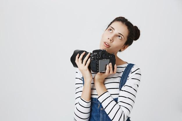 Ragazza creativa premurosa che tiene macchina fotografica professionale e guardando nell'angolo in alto a sinistra, pensando