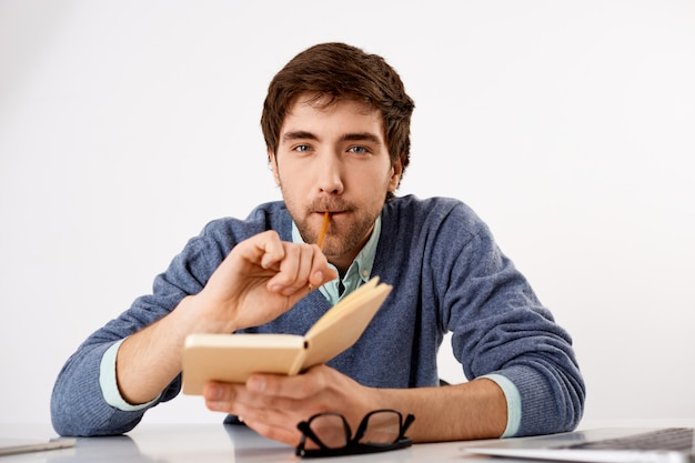 Thoughtful, creative male journalist or writer, biting pencil, holding notebook, writing schedule, look thinking