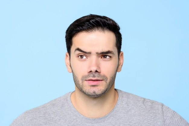 Thoughtful curious young man face with eyebrow raised isolated
