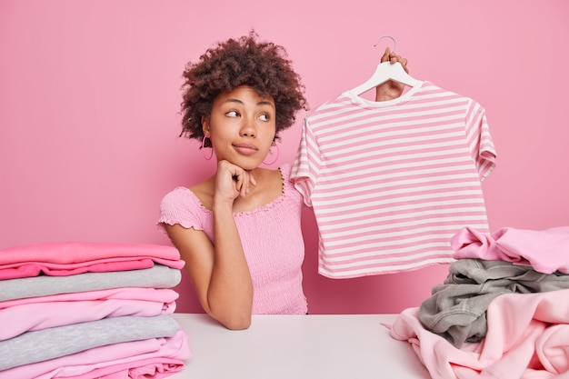 Thoughtful curly afro american woman holds striped t shirt on hanger folds clean clothes poses at white table poses against pink wall. household duties concept. perfect housewife at home
