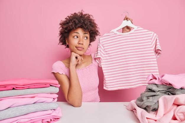 Задумчивая кудрявая афро-американка держит полосатую футболку на вешалке, складывает чистую одежду, позирует на белом столе у розовой стены. концепция домашних обязанностей. идеальная хозяйка дома