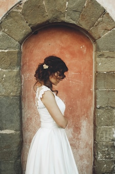 Thoughtful curly bride stands before an old stone wall