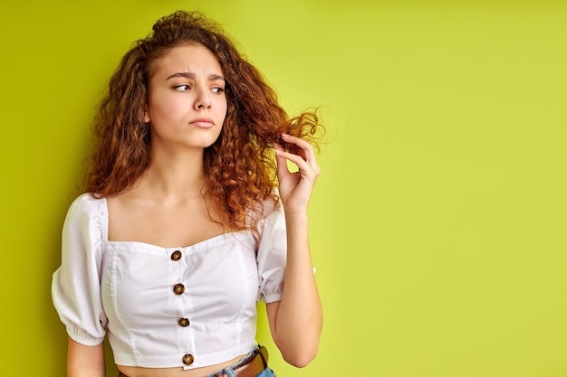 Thoughtful curly girl is looking at split ends of hair, examine it, want to cut out