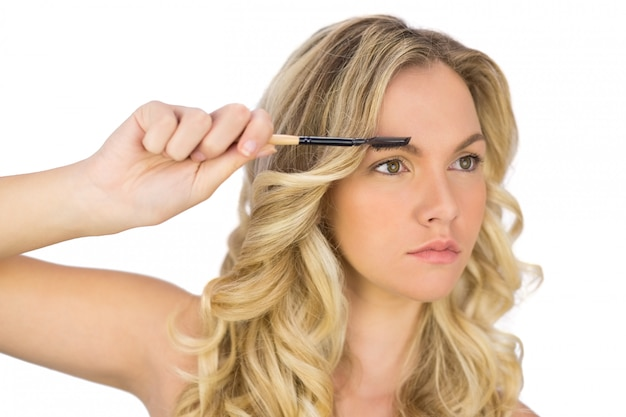 Thoughtful curly haired blonde using eyebrow brush