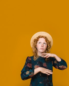 Thoughtful curly redhead woman in studio