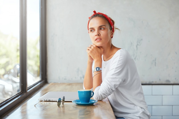 Thoughtful cute female blogger dressed in casual clothing, sits at coffe shop, contemplates about something as looks into window, uses laptop computer, drinks hot beverage, has break after work
