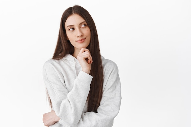 Thoughtful cute girl with long hair looking aside and smiling while thinking, standing pensive, making choice, imagine something interesting, white wall