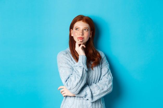 빨간 머리를 가진 사려 깊은 귀여운 여자, 왼쪽 상단 모서리 로고를 찾고 생각, 뭔가 이미징, 파란색 배경 위에 서.