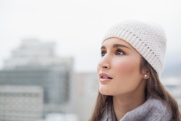 Thoughtful cute woman with winter clothes on posing