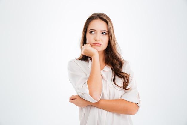 思いやりのあるかわいい若い女性が立って白い壁を考えて