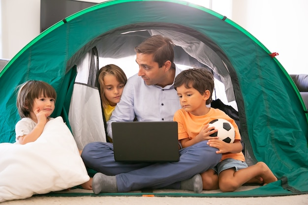 Thoughtful dad sitting cross-legged with kids in tent at home and holding laptop. cute children watching movie on portable computer with caucasian father. childhood, family time and weekend concept