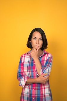 アイデアを考えてカメラを探している思いやりのある黒髪の女性。顔の表情、感情、感情。黄色の背景に格子縞のシャツを着た女性。