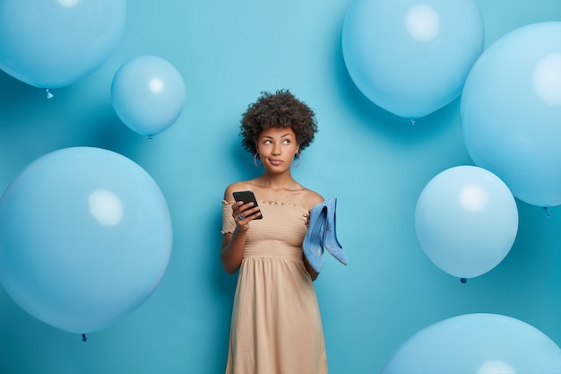 Thoughtful dark skinned curly haired woman in fashionable dress holds mobile phone and sends invitations to friends balloons theme party chooses best shoes to wear surrounded by inflated balloons