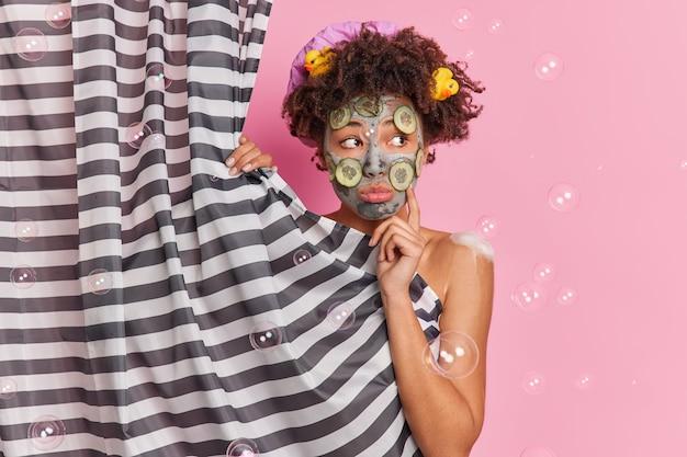 사려 깊은 어두운 피부 곱슬 여자는 슬프게도 옆으로 보이며 피부 회춘을 위해 오이 조각으로 영양 점토 마스크를 적용합니다. 분홍색 배경 위에 절연 샤워 커튼 뒤에 알몸으로 서