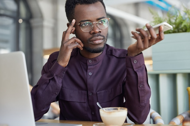 Thoughtful dark skinned male eneterpreneur in eyewear, has coffee break after hard work, makes business report on laptop computer