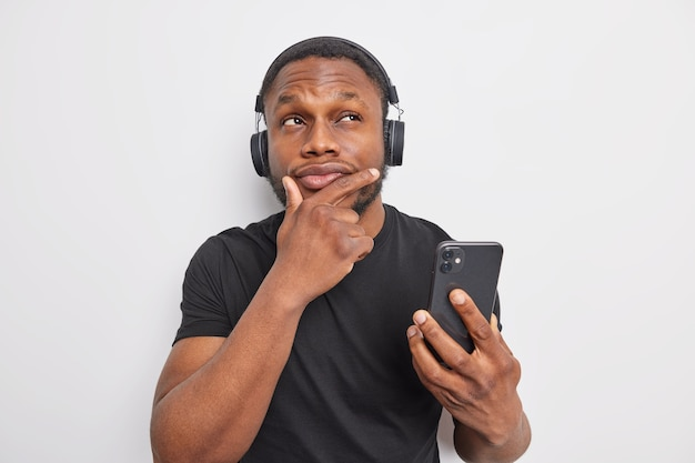 Thoughtful dark skinned man holds chin has pensive expression uses mobile phone and stereo headphones for listening to  to music stands pensive indoor against white background. let me think about it
