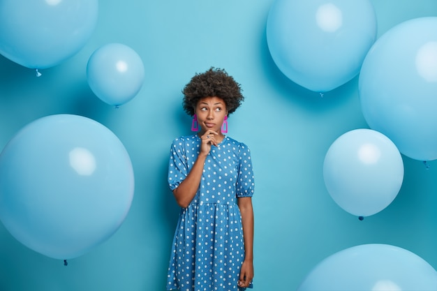 사려 깊은 짙은 피부의 여성은 물방울 무늬 블루 드레스를 입고 풍선 파티에 있고 세련된 의상을 입고 잠겨있는 표정을 지으며 생일을 축하합니다. 여가 시간, 파티 개념