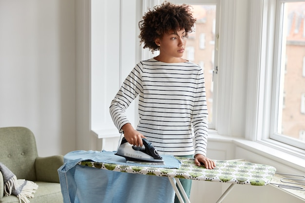 Thoughtful dark skinned young housewife in striped clothes irons clothes on ironing board, uses electric iron stands, looks out of window