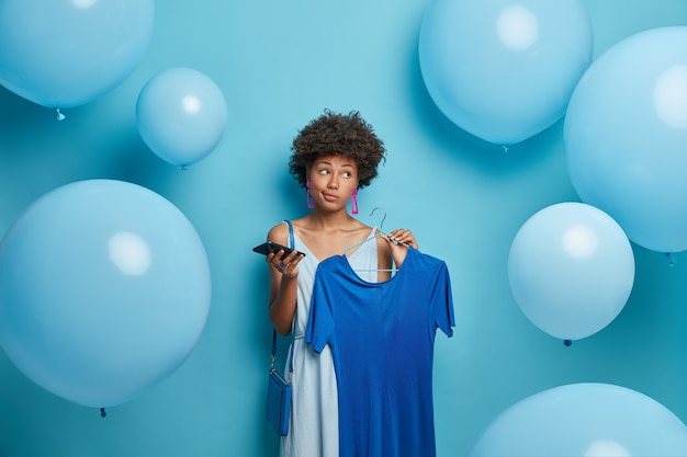 Thoughtful dark skinned young woman has curly hair, holds elegant blue dress on hanger, mobile phone in hand, dresses for theme blue party, looks aside, poses against balloons with pensive look