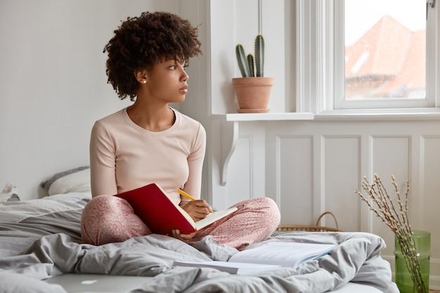 사려 깊은 어두운 피부를 가진 젊은 여성이 교과서에 글을 쓰고, 연꽃 자세로 앉아 있고, 잠옷을 입고, 아늑한 침실에 혼자 앉아 있고, 에세이를 쓰기위한 창의적인 아이디어에 대해 생각하고, 창문 옆에 집중합니다.