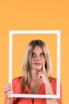 Thoughtful deaf woman holding frame cutout on yellow background