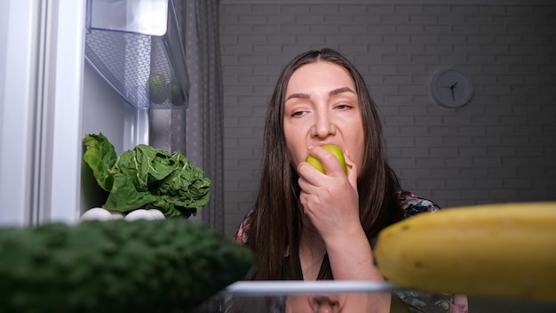 Thoughtful dieting woman looks for snacks and chooses fresh green apple from shelf in dark kitchen at night close view from inside fridge