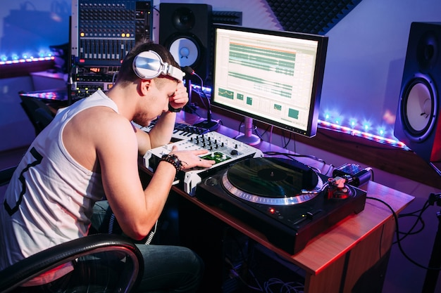 Thoughtful dj adjusting sound in recording studio