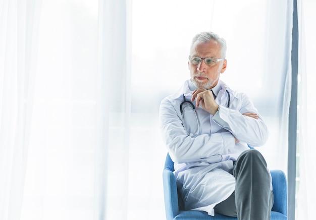 Medico premuroso sulla sedia che osserva via