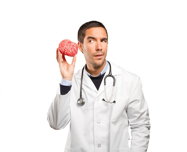Thoughtful doctor holding a toy brain against white background