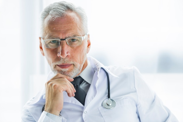 Thoughtful doctor looking at camera