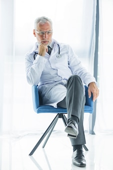 Thoughtful doctor sitting on chair