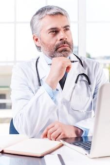 사려깊은 의사. 사려깊은 성숙한 회색 머리 의사가 턱에 손을 대고 작업장에 앉아 시선을 돌리고 있다
