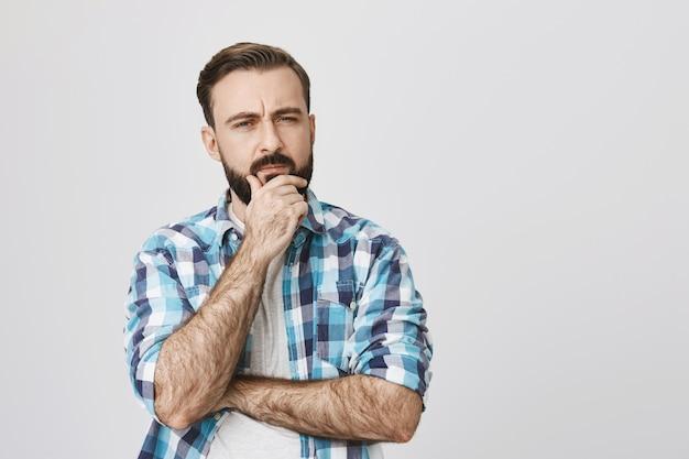 Uomo barbuto dubbioso premuroso pensando, prendere una decisione