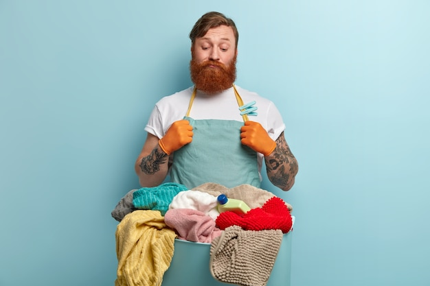 Задумчивый, сомневающийся, нерешительный мужчина с густой рыжей бородой смотрит на белье, не умеет стирать, стирать не горит